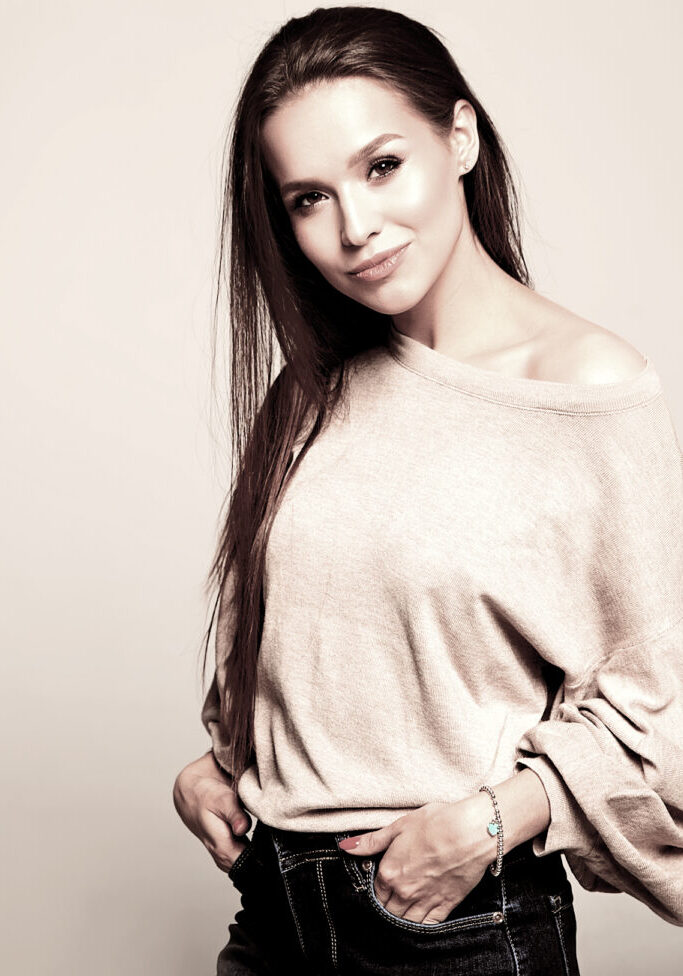 Portrait of beautiful smiling cute brunette woman model in casual beige warm sweater clothes with no makeup isolated on gray